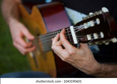 The guy is playing the guitar. Hand takes a chord closeup.