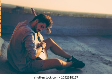 Guy playing the guitar on a building rooftop, relaxing and enjoying hot summer days