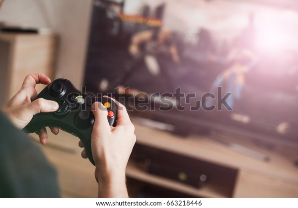 The guy is playing on the console