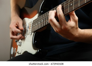 The guy plays the electric guitar on a black background.