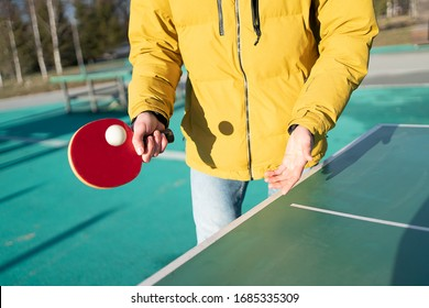 guy plays table tennis pingpong on the street. racket and ball with a tennis green table. hands in the frame and racket. in a yellow jacket in cold weather
