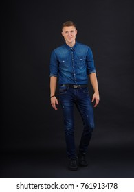 A guy poses by bending one leg against a black background
