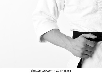 Guy poses in white kimono with black belt, close up. Male torso and sportive arms on white background. Karate fighter with fit strong hands gets ready to fight. Healthy lifestyle and jujitsu concept.