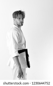 Guy poses in white kimono with black belt. Healthy lifestyle and jujitsu concept. Man with serious face and bristle isolated on white background, copy space. Karate fighter with fit strong body