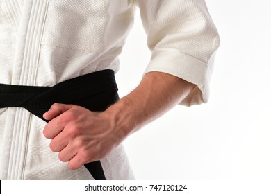 Guy poses in white kimono with black belt, close up. Karate fighter with fit strong hands gets ready to fight. Male torso and sportive arms on white background. Japanese karate and sports concept