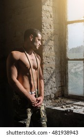 Guy posing without shirts in army pants