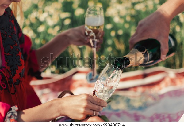 The guy pours champagne in a glass at a picnic