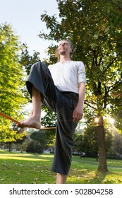 Guy practising slack line in the city park