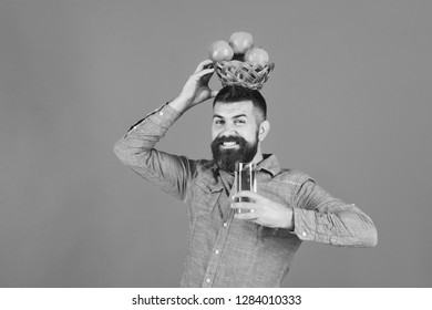 Guy presents homegrown harvest. Farming and autumn products concept. Man with beard holds bowl of fruit and juice on blue background. Farmer with happy face holds fresh apple juice and apples on head