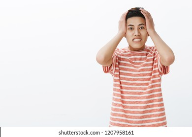 Guy pressing hands to head and clenching teeth being anxious and concerned having troubles forgetting to make important task in time, standing perplexed and upset with nervousness over white wall