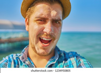 Guy with protection lotion on the face taking a selfie or making live video stream. The man is on vacation, and he smeared with sunblock, and holds it in his hand.