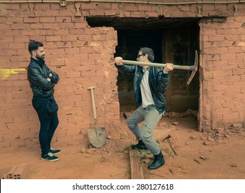 Guy pulling down a wall while another one is watching