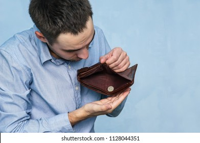 The guy pulls out the last ruble out of an empty purse. Poverty and unemployment. Man with no money. Businessman holding empty wallet.