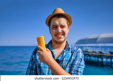 Guy put sun cream on the face. Man is on vacation, and he smeared with sunblock, and holds it in his hand.