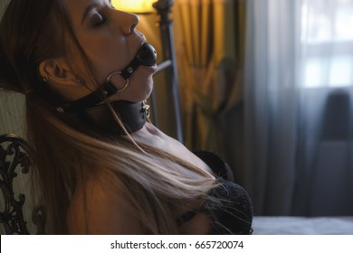 guy puts the gag in girl's mouth. BDSM concept. Gag closeup. Sexy couple play in love games