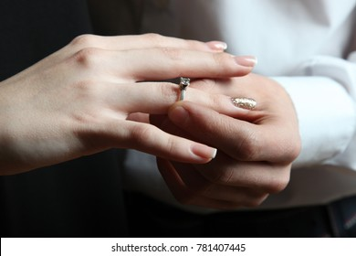 The guy puts the ring on the girl's finger. Close-up.