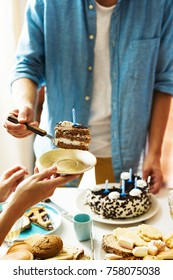 Guy putting piece of birthday cake with blown candle on saucer of guest