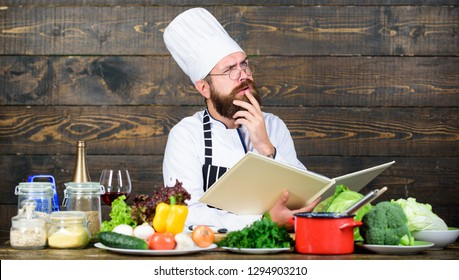 Guy read book recipes. Culinary arts concept. Man learn recipe. Try something new. Cookery on my mind. Improve cooking skill. Book recipes. According to recipe. Man bearded chef cooking food.