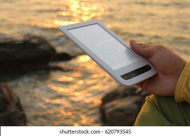 The guy is reading an e-book at sunset. The guy is reading an e-book at sunset. Self-education and a free lifestyle in the journey.