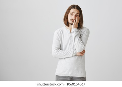 Guy is ready to sleep while standing. Portrait of tired handsome caucasian man leaning head on palm, being bored and uninterested, wanting to escape from boring meeting, looking indifferent at camera