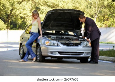 The guy repairs the car, the girl looks at him and smiles