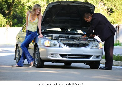 The guy repairs the car, the girl smiles