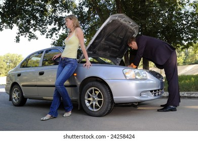 The guy repairs the car, the girl stands nearby