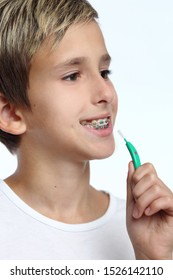 Guy with retainer for teeth brushing teeth on a white background.