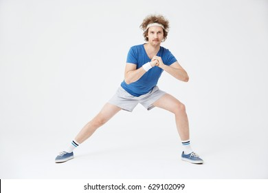 Guy in retro sport suit doing stretching exercises. White background