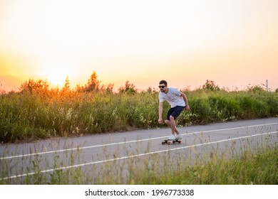 a guy rides a longboard skateboard on the road against the background of the sunset