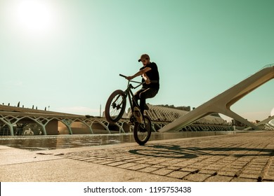 Guy riding a bmx bike on the street. Freestyle BMX in the city, extreme sports concept