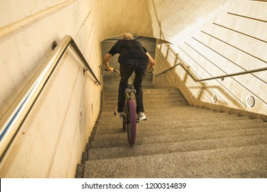 Guy riding a bmx bike through the streets of the city. Guy going down some stairs with a bmx bike.