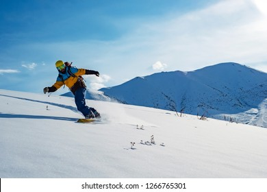 The guy is riding a snowboard. In the mountains in pristine snow. Mountains of Kyrgyzstan