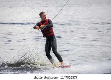 the guy is riding a wakeboard on the river. Active and Extreme Sports
