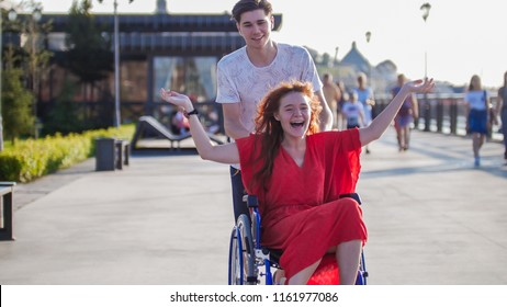 Guy Rolls A Disabled Beautiful Girl In A Wheelchair Outdoors