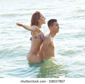 guy rolls a girl on a floating over the waves