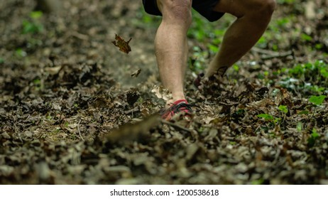 the guy is running down a steep hill while participating in an ocr race
