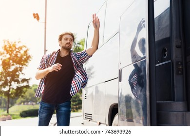 The guy runs after the bus that leaves. He missed the bus and tries to catch up with him. He runs after a modern black bus and waves his hand to stop it.