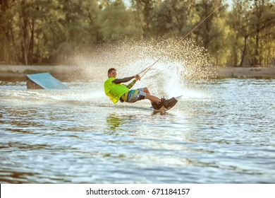 Guy rushes along the lake on the board, extreme sport wakeboarding.