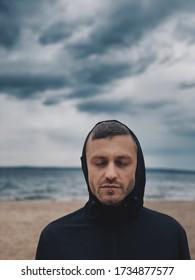un gars en mer avec les yeux fermés dans un capot sur un fond nuageux