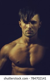 ?oung guy with serious face and sexy athletic muscular bare torso posing on black background