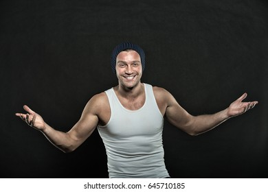 guy or sexy happy man with muscular hands in white vest and hat posing in studio on black background