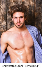 Guy shimmering skin undressing bathrobe. Sexy attractive macho tousled hair on wooden background. Man athlete with fit torso. Sportsman show six pack sexy torso. Bachelor sexy body chest and belly.