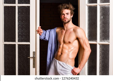 Guy shimmering sweaty skin wear bathrobe. Man athlete with fit sexy torso. Sexy lover concept. Sexy attractive macho tousled hair coming out through bedroom door. Bachelor sexy body chest and belly.