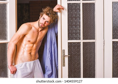 Guy shimmering sweaty skin wear bathrobe. Man athlete with fit sexy torso. Sexy lover concept. Bachelor sexy body chest and belly. Sexy attractive macho tousled hair coming out through bedroom door.