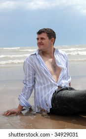 The guy in a shirt sits on sand