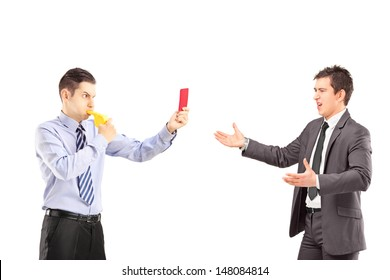Guy showing a red card and blowing a whistle to a young businessman in suit, isolated on white background