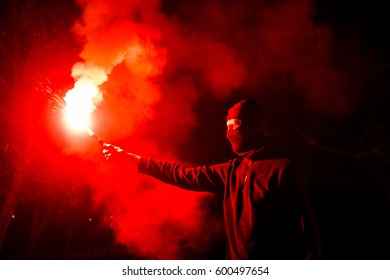 Guy with a signal rocket in his hands. Revolution in Ukraine. Anniversary of Euro-Maidan. Ultras is a football fan.