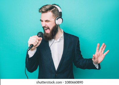 Guy is singing in microphone. Also he has the headphones on his hand. He is singing very emotional. Isolated on blue background