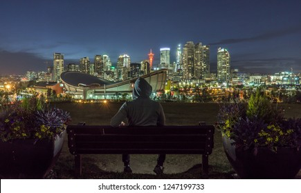 Guy is siting at a bench and watching Calgary downtown